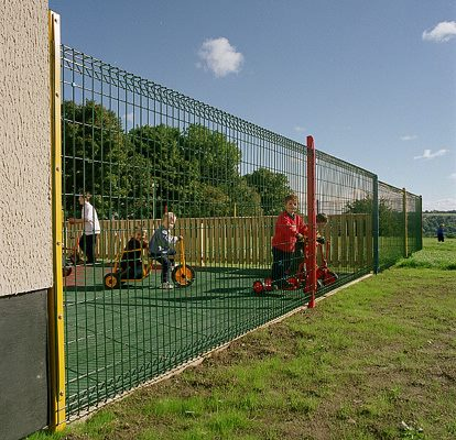 Roll top mesh panel fence provides demarcation and containment for a childs play area.