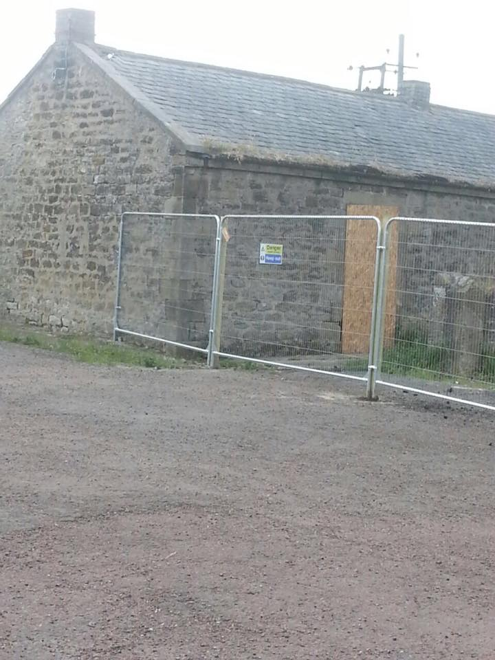Temporary fencing erected around derelict farm buildings