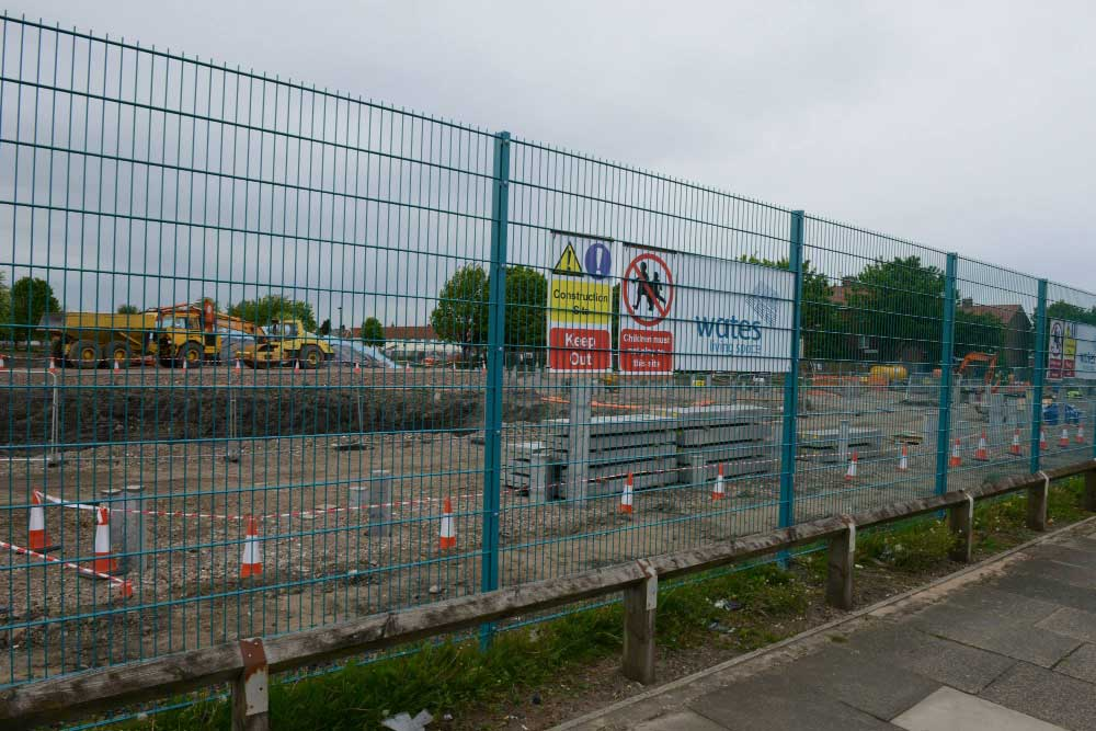 Twin wire mesh fence erected as temporary perimeter fence for building site and finished in Wates corporate colours.